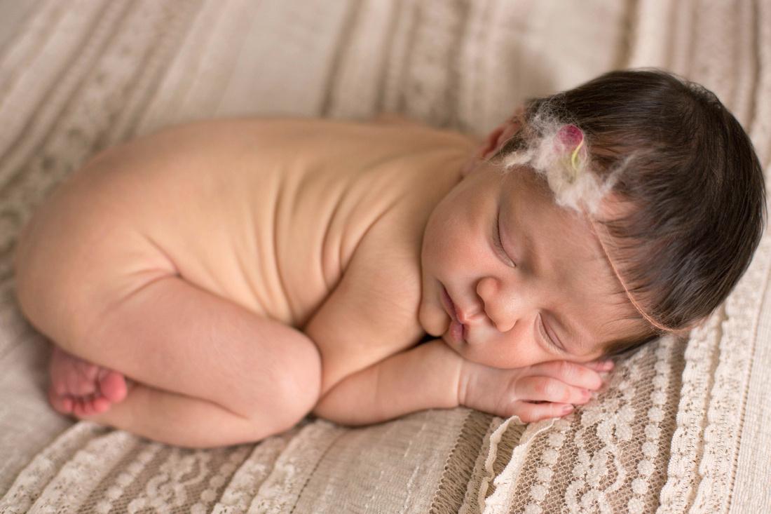 Sleeping newborn Evalynn with flower headband by Pueblo newborn photographer.