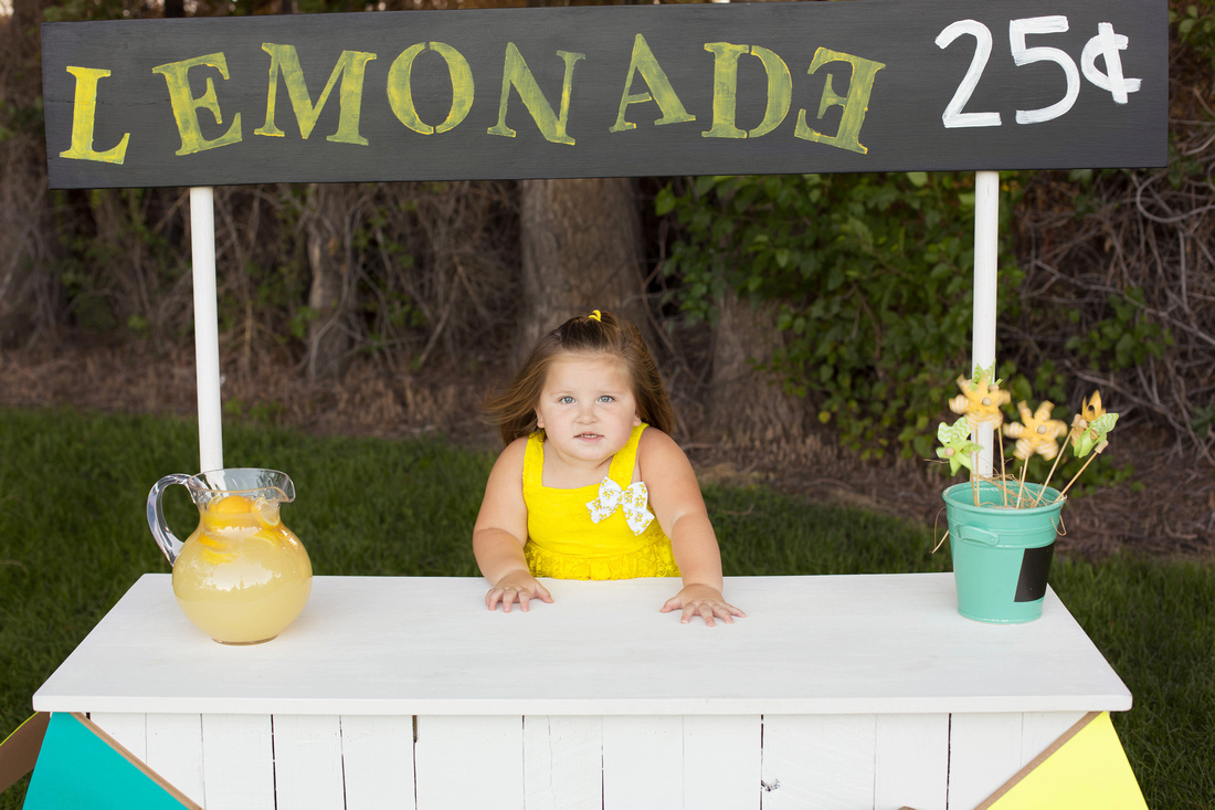 Madison behind the lemonade stand by Pueblo Children's photographer K.D. Elise Photography